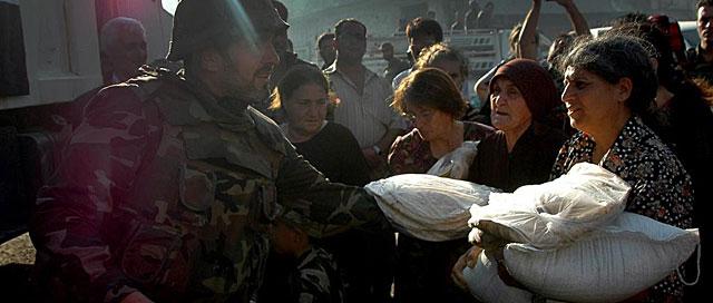 Varias mujeres reciben alimentos de un soldado sirio en Quseir.   Efe