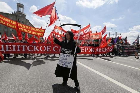 Un detractor de Putin sostiene una guadaña durante la manifestación en Moscú.   Efe