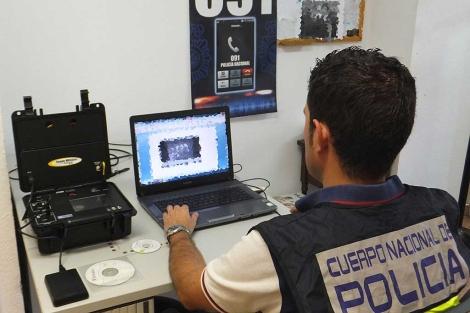 Un agente examina parte del material intervenido. | Foto: CNP.