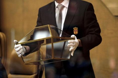 Un funcionario de la Asamblea de Madrid transporta la urna de las votaciones de la Cámara.