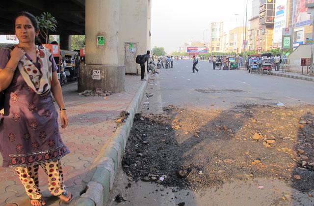 Una mujer espera con gesto serio en la avenida GM de Gurgaon. | David Jiménez