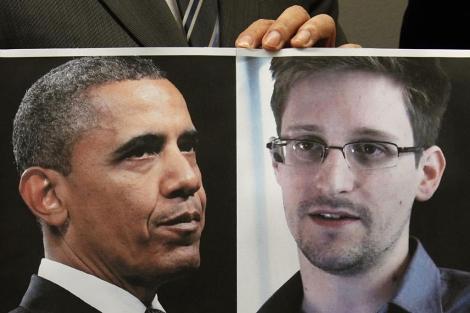 Un abogado chino muestra una pancarta con las fotos de Obama y Snowden. | Reuters