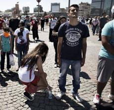 Una chica le da agua a un manifestante.| Afp
