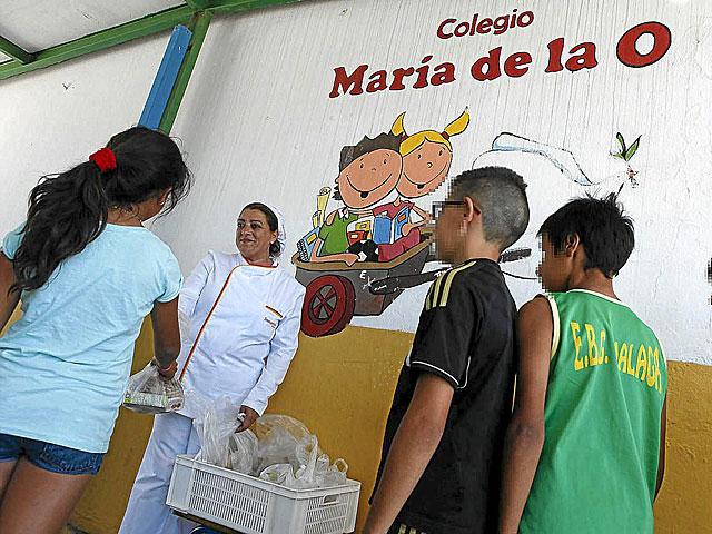 Tres niños reciben la merienda en un colegio de Málaga.   Jesús Domínguez