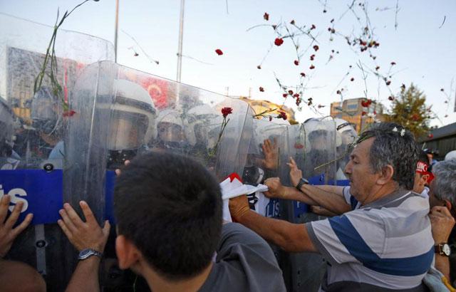 Un grupo de manifestantes trata de frenar a los agentes en medio de una lluvia de claveles. | Reuters