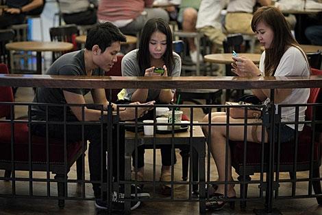 Usuarios de móviles en Bangkok.   Afp
