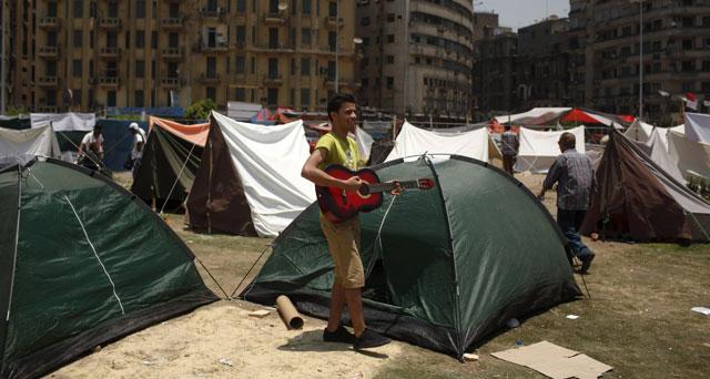 Un manifestante toca una guitarra junto a una tienda en la plaza cairota de Tahrir. | Reuters