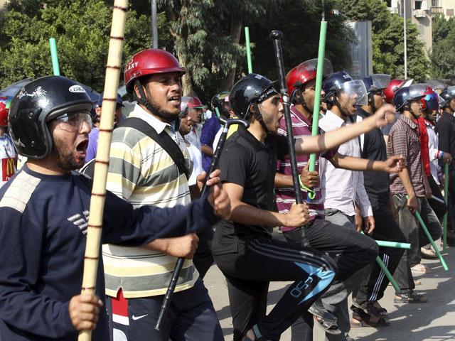 Simpatizantes del presidente Mursi con palos y cascos en El Cairo. | Afp