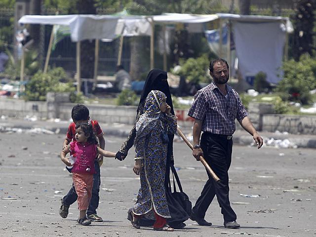 Un 'hermano musulmán', armado con un palo, y su familia en una calle de El Cairo. | Reuters
