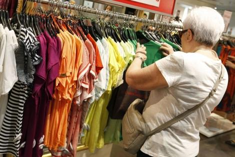 Una señora ojeando ropa en una tienda. | Javier Lizón