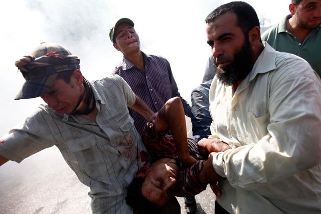 Manifestantes a favor de Mursi trasladan a un herido.| Afp [VEA MÁS FOTOS]