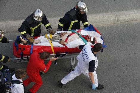 Los bomberos y el SAMU de París llevan en camilla a una víctima.| Reuters