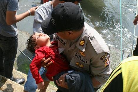 Un policía rescata a un niño del naufragio cerca de Java. | Afp