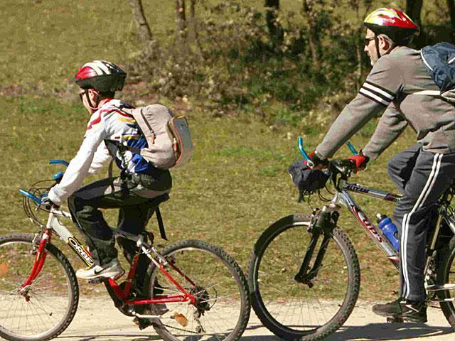 Un hombre y un niño pasean en bicicleta. | EL MUNDO