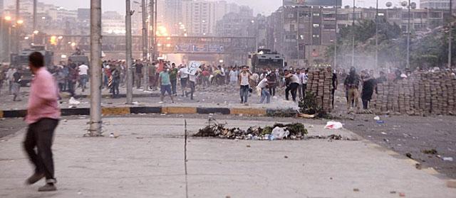 Un partidario de Mursi corre mientras oponentes lanzan piedras. | Reuters [MÁS IMÁGENES]