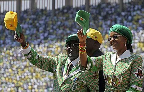El presidente Mugabe saluda a sus seguidores junto a su esposa Grace.   Afp