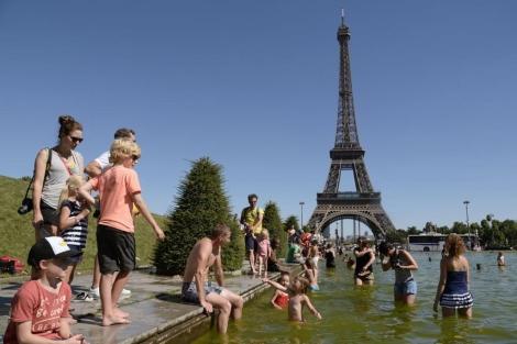 Personas que se refrescan cerca de la Torre Eiffel en París. | Afp
