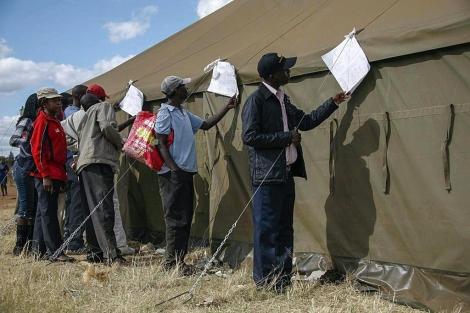 Varios ciudadanos miran los resultados electorales en un distrito de Harare. | Efe