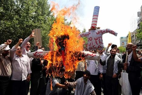 Los manifestantes queman un muñeco con la bandera de EEUU. | Afp