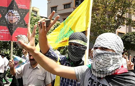 Dos hombres con pañuelos palestinos y piedras en Teherán. | Efe