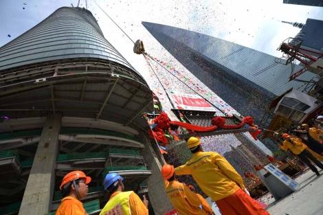 Obreros observan la colocación de la última viga de la torre de Shanghái | Afp
