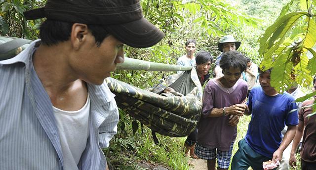 El padre, en camilla, y el hijo, con camiseta violeta, al abandonar la jungla. | Efe