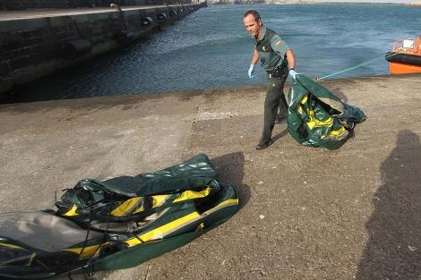 Un Guardia Civil recoge las lanchas en las que venían los inmigrantes.   Fco. Ledesma