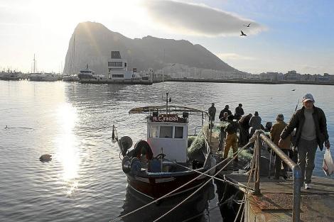 Pescadores de La Línea llegan a puerto con la Roca al fondo.