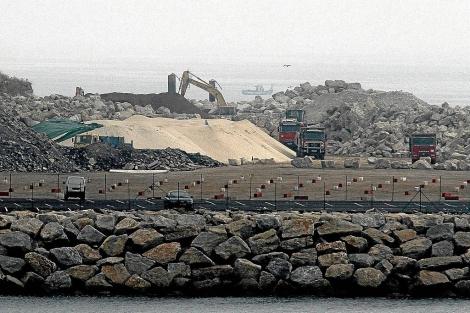 Varias maquinas y camiones trabajando con la arena de la duna. | Efe