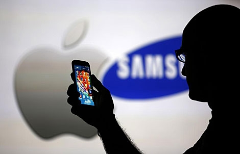 Imagen de los logos de Apple y Samsung con un Galaxy S4 en primer plano. | Reuters