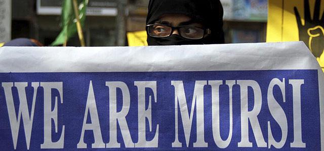 Un hombre levanta un cartel de apoyo a Mursi en Pakistán.   Efe