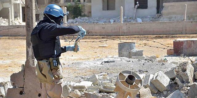 Uno de los miembros de la ONU toma muestras en Zamalka (Damasco). | Foto: Efe