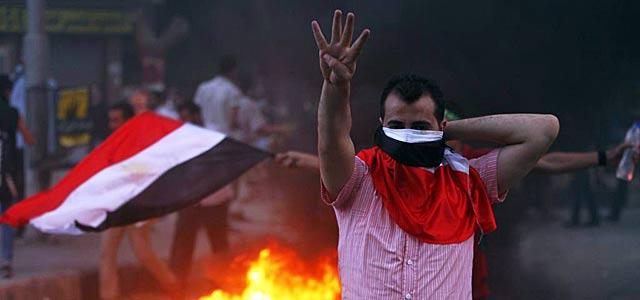 Un simpatizante de Mursi hace el signo Rabaa, símbolo de las protestas islamistas.   Reuters