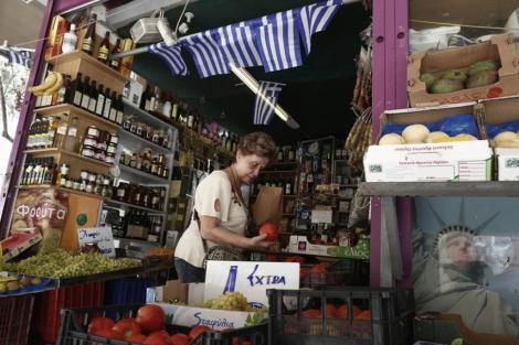 Una mujer compra fruta en una tienda en Atenas.  Reuters