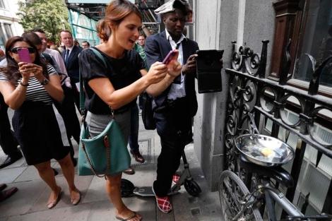 Una mujer hace una foto de los huevos fritos por el reflejo del rascaciolos.   Reuters