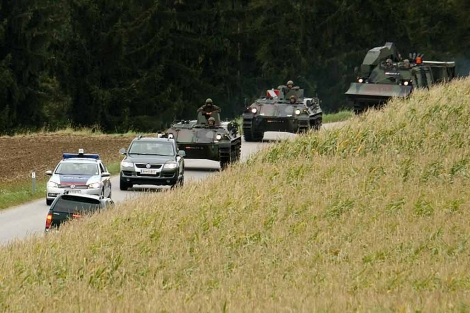 Vehículos militares se dirigen a la granja donde sigue atrincherado el sospechoso.   Reuters