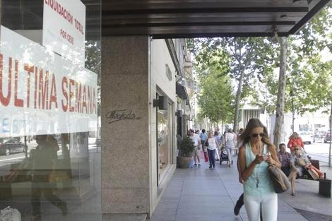 Una joven pasa frente a un escaparate de una tienda cerrada en Serrano.   B. Díaz