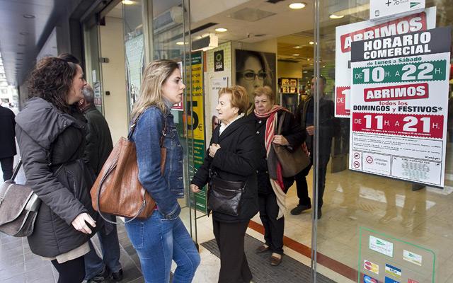 Varios clientes entran a un centro comercial abierto un domingo en Valencia. | Benito Pajares