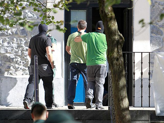 Agenets de la Guardia Civil custodian a uno de los detenidos. | Javier Etxezarreta / Efe