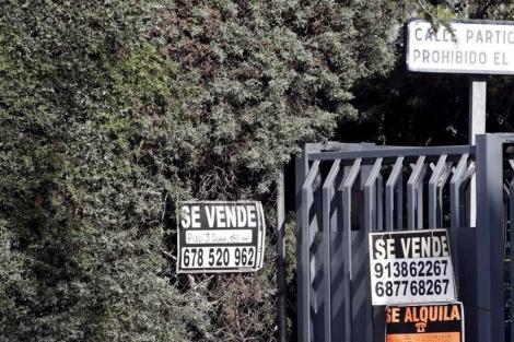 Carteles de 'Se vende' y de 'Se alquila' en la entrada a una urbanización.   C. Barajas