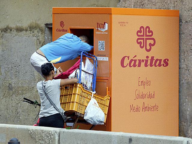 Dos personas cogen ropa de un contenedor de Cáritas en Valencia. | Benito Pajares