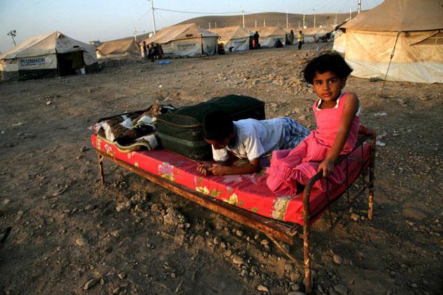 Dos niños kurdos de Siria, en medio de un campo de refugiados. | Afp