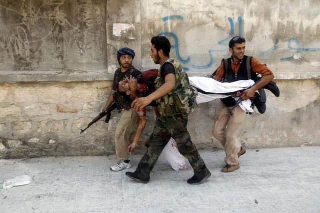 Miembros del Ejército Libre Sirio trasladan a un reblede herido en Alepo.   Reuters