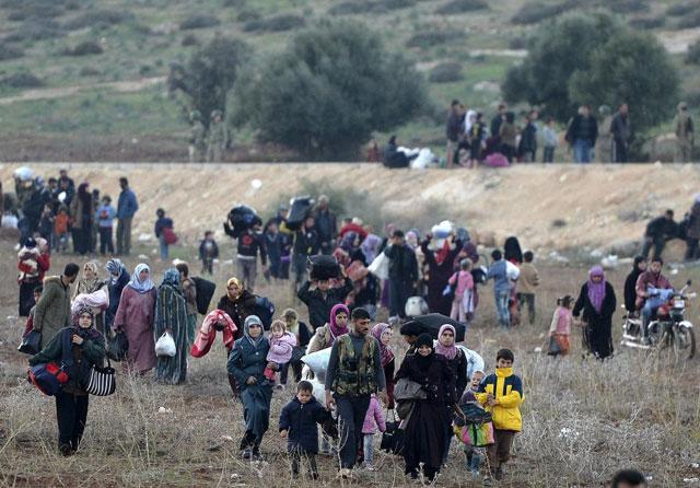 Refugiados sirios avanzan campo a través hacia un campamento de refugiados en Turquía. | Afp