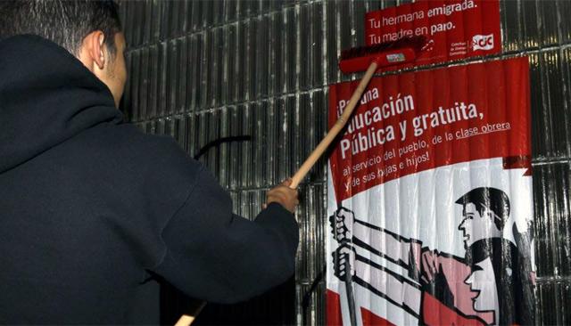 Un joven cuelga un cartel informativo de la huelga. | Efe