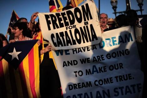 Manifestantes muestran banderas y pancartas frente al Palacio de Pedralbes. | Afp