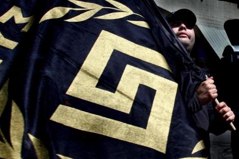 Un miembro de 'Amanecer Dorado' con una bandera de la formación.