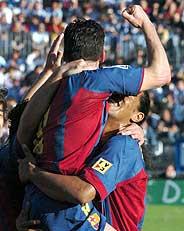 Ronaldinho sostiene a Giuly en la celebración de su primer gol. (Foto: EFE)