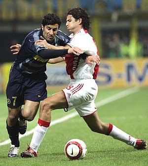Luis Figo se marcha de un jugador del Ajax durante el encuentro. (Foto: AP)
