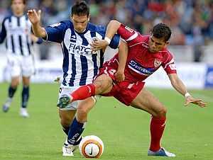 Daniel Alves y Mark González luchan por hacerse con el balón. (Foto: EFE)